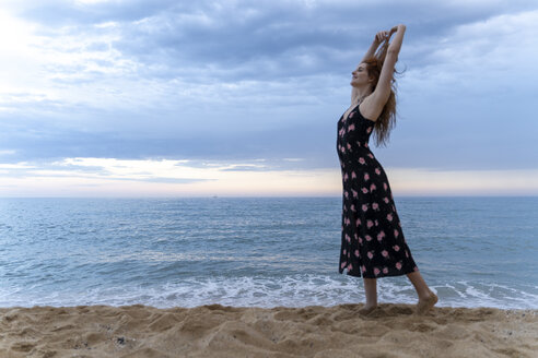 Happy young woman dancing on the beach in the evening - AFVF03014