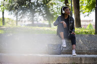 Woman resting in urban park with cell phone and headphones - GIOF06351