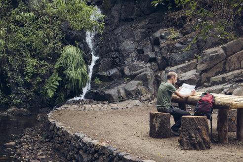 Hiker taking a break at rest area, Barranco el Cedro, La Gomera, Canary Islands, Spain - MAMF00683