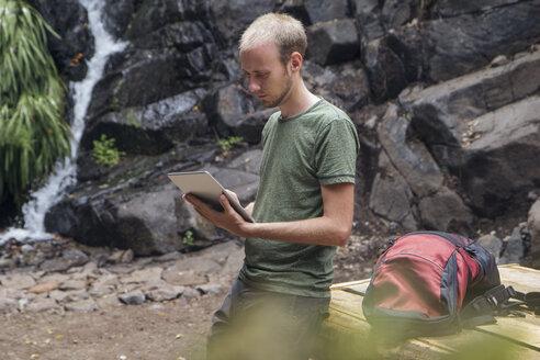 Hiker taking a break at rest area and using tablet, Barranco el Cedro, La Gomera, Canary Islands, Spain - MAMF00686