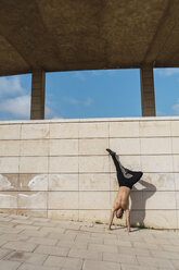 Young man doing a handstand at a wall outdoors - AFVF03021