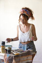Young woman painting in art studio - JPTF00056