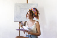 Young female painter in art studio next to empty canvas - JPTF00059