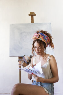 Young female painter in art studio next to empty canvas looking at papers - JPTF00062