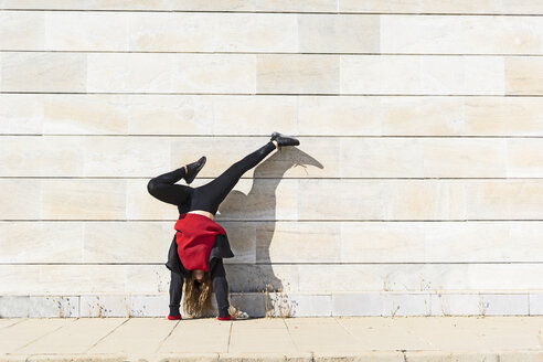 Teenage girl doing a handstand at a wall outdoors - ERRF01395
