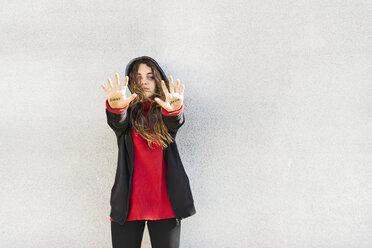 Portrait of serious teenage girl showing the words fight and sexism written on her palms - ERRF01398