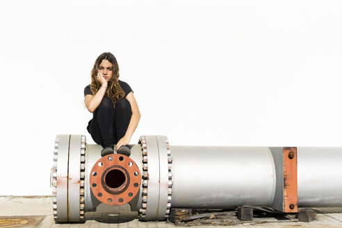Portrait of serious teenage girl sitting on large pipe - ERRF01407