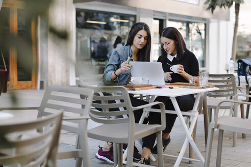 Two friends sitting together at a pavement cafe using laptop - OCAF00391