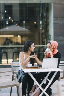 Two friends sitting together at a pavement cafe with laptop talking - OCAF00400
