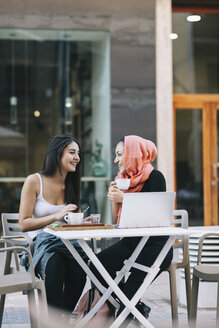 Two happy friends sitting together at a pavement cafe with laptop - OCAF00403