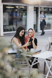 Two friends sitting together at a pavement cafe using cell phone - OCAF00406
