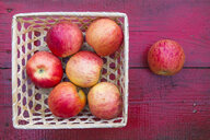 Close up of basket of red apples on red wooden table - BLEF04442