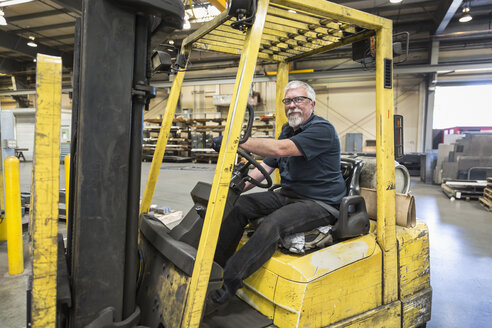 Caucasian worker driving forklift in factory - BLEF04457