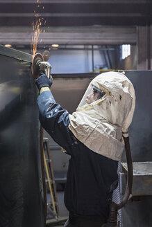 Caucasian worker grinding metal container in factory - BLEF04469