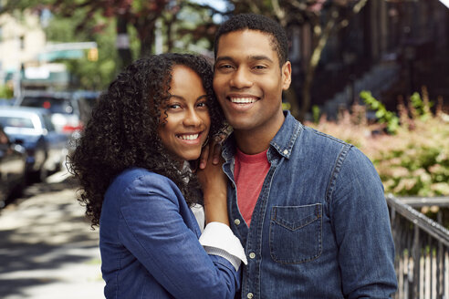 Smiling couple posing on city sidewalk - BLEF04514