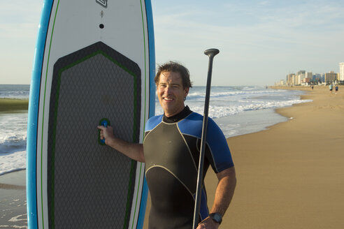 Man posing with paddleboard on beach - BLEF04532
