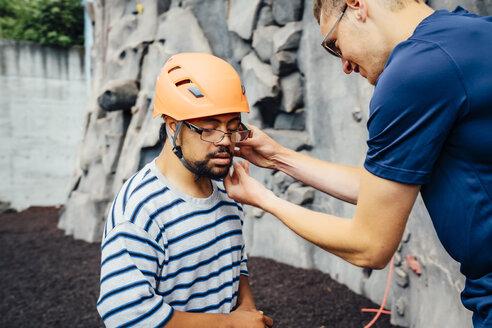Man helping rock climber fasten helmet - BLEF04586