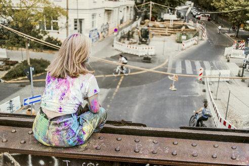 Girl with Holi colours on her clothes sitting on bridge, Germany - VGPF00042