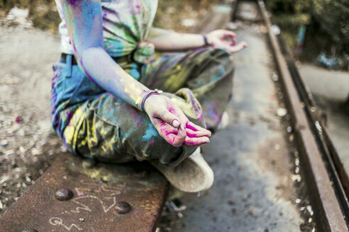 Girl with Holi colours on her clothes sitting on bridge, meditationg, Germany - VGPF00045
