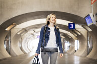 Smiling woman standing in underpass at the station - HMEF00404