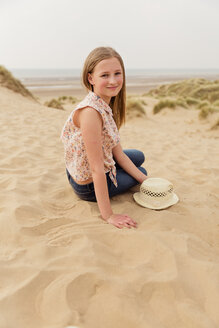 Portrait of smiling girl sitting on the beach - NMS00306