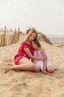Two girls hugging on the beach - NMS00309