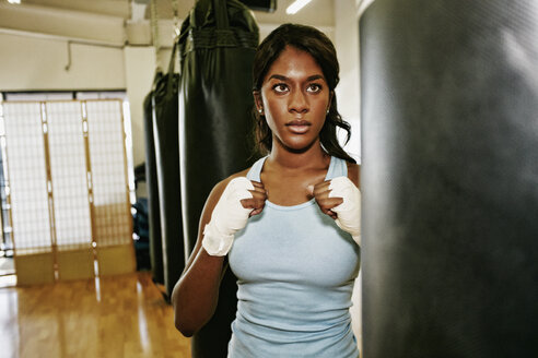 Black woman staring at heavy bag in gymnasium - BLEF04608