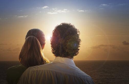 Smiling Caucasian couple admiring sunset at ocean - BLEF04683
