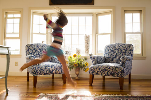 Carefree Caucasian girl running and jumping in livingroom - BLEF04695