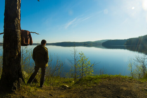 Caucasian man standing at lake admiring scenic view - BLEF04737