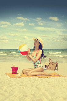Caucasian woman holding beach ball on beach - BLEF04764
