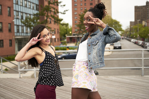Smiling women gesturing peace on city boardwalk - BLEF04791