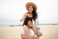 Man carrying woman on shoulders at beach - BLEF04797