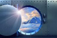 Open vault door revealing mountaintop above clouds - BLEF04806
