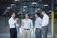 Businessmen talking in empty warehouse - BLEF04866