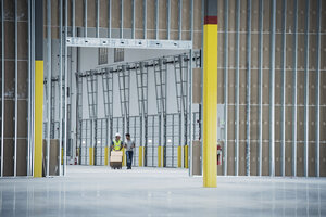 Workers with boxes on hand truck in empty warehouse - BLEF04872