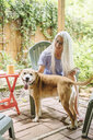 Caucasian woman holding cell phone petting dog on backyard patio - BLEF04902
