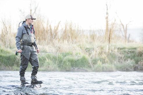 Caucasian man fly fishing on rock in river - BLEF04971