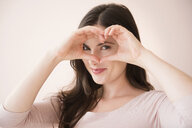 Caucasian woman gesturing heart-shape with hands over eyes - BLEF05085