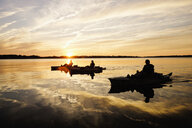 Silhouette of people fly fishing in kayaks on river - BLEF05106