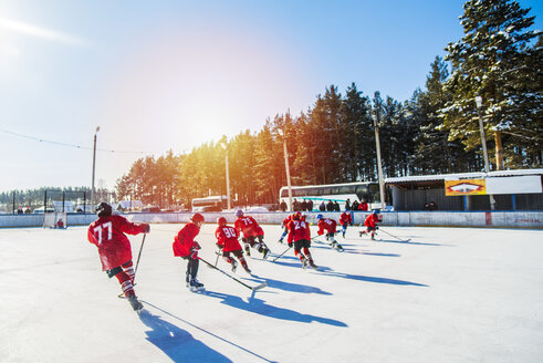 Caucasian boys playing ice hockey outdoors - BLEF05121