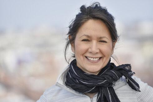 Smiling Hispanic woman wearing scarf - BLEF05226