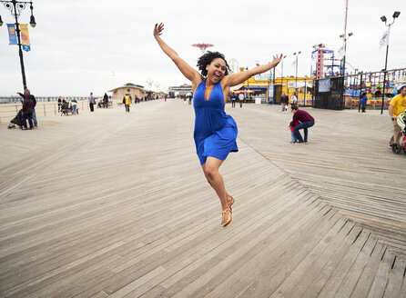 Woman smiling and jumping on boardwalk at amusement park - BLEF05262