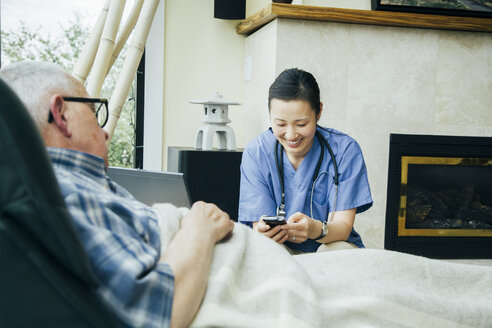 Nurse texting on cell phone near patient - BLEF05298