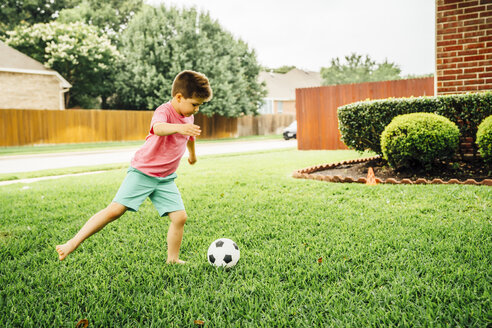 Caucasian boy kicking soccer ball on lawn - BLEF05331