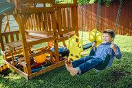 Smiling Caucasian boy n swing in backyard - BLEF05352