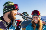 Couple carrying skis on snowy mountain - BLEF05484