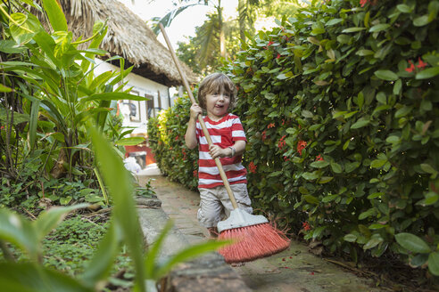Caucasian boy playing with broom on path near house - BLEF05508