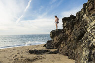 Caucasian girl standing on rocks at beach - BLEF05541