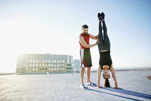 Caucasian man helping woman do handstand on urban rooftop - BLEF05556